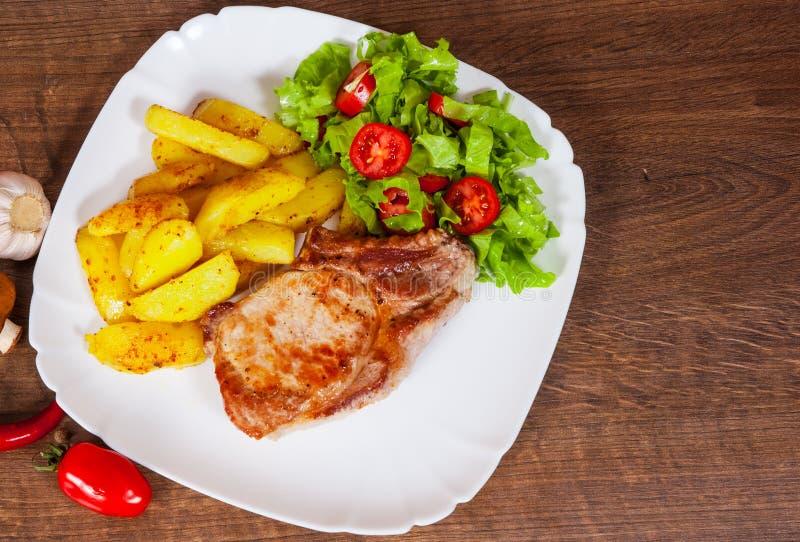 Saftig grillad köttfilébiff med den stekt potatisen och grönsaksallad royaltyfri bild