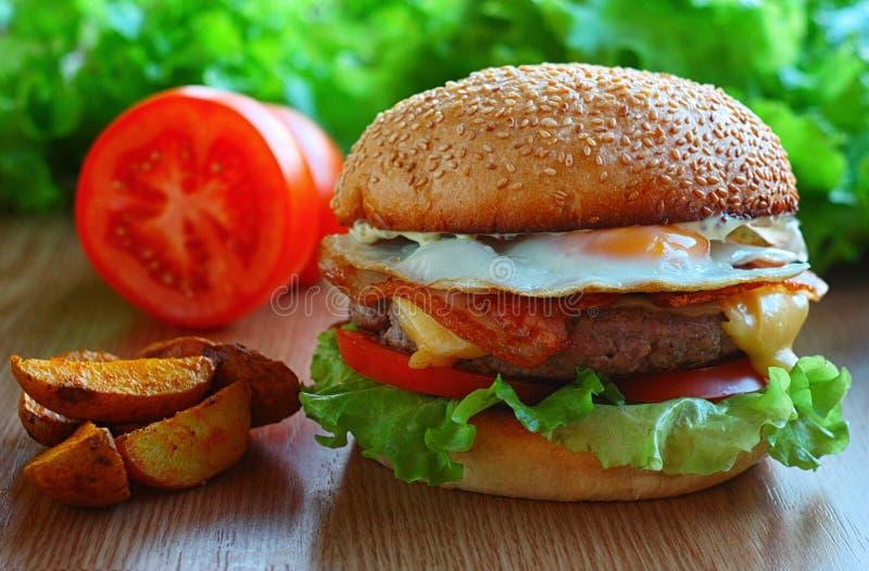 Saftig hamburgare med nötköttlappen, ost, bacon, tomater, sallad, vaktelägg På tabellen bland nya grönsaker arkivbilder