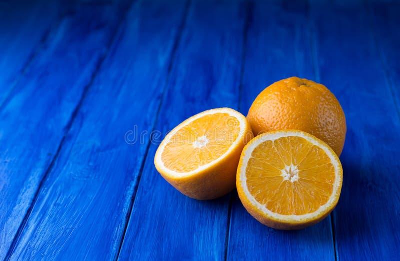 Saftig hel apelsin och två halvor på mörkret - blå träbakgrund fotografering för bildbyråer