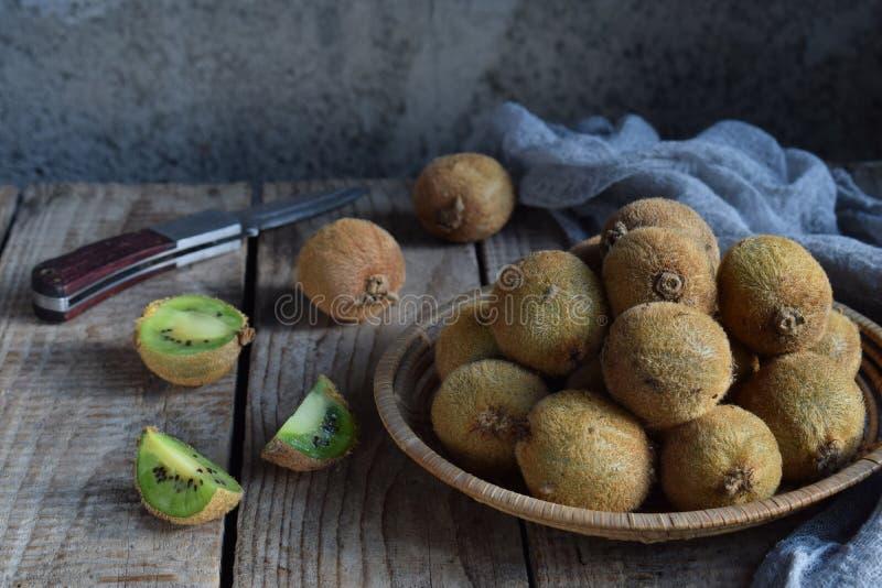 Saftig hel och skivad kiwi på trätabellen sund mat Tropisk kivifrukt 1 livstid fortfarande royaltyfri bild