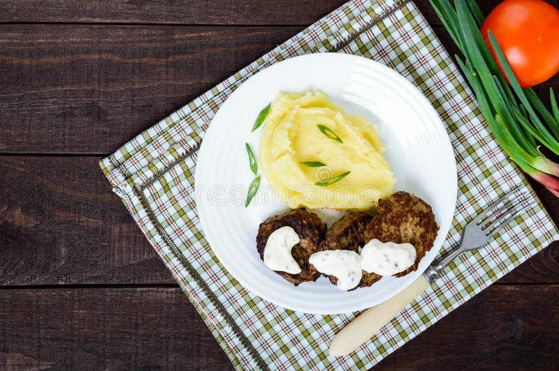 Saftig leverkotlett med sås och mosade potatisar på en vit platta royaltyfri foto