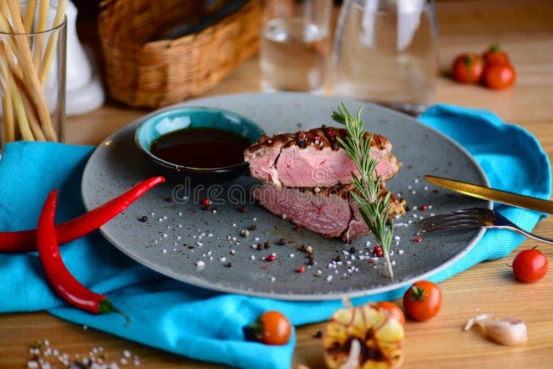 Saftig medelsällsynt nötköttbiff på en platta i en restaurang många bakgrundsklimpmat meat mycket arkivfoto