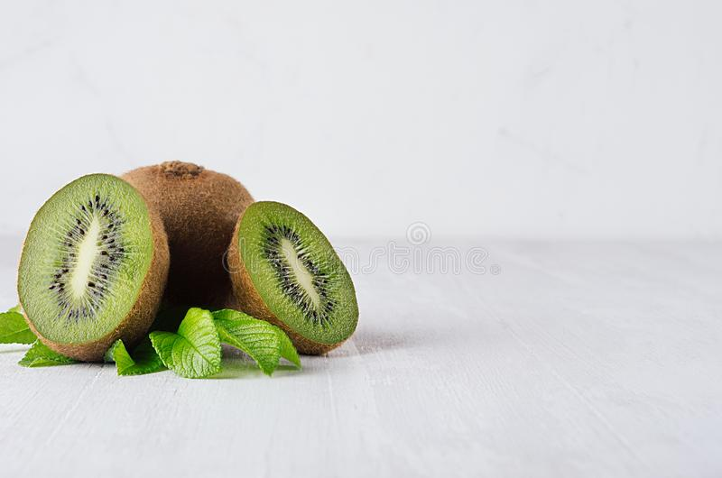 Saftig ny kiwi med skivan, sidacloseup på vit träbakgrund, kopieringsutrymme fotografering för bildbyråer