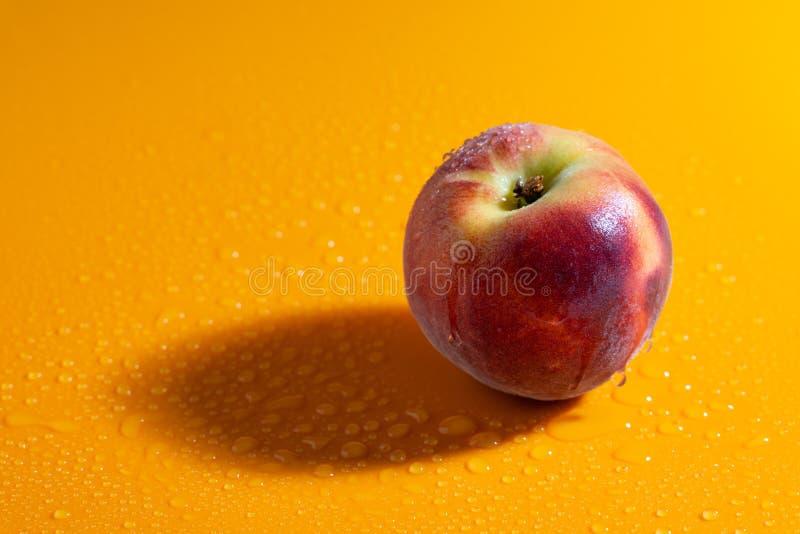 Saftig ny mogen persika på en orange matte bakgrund med vattendroppar frukter och sund mat royaltyfri bild
