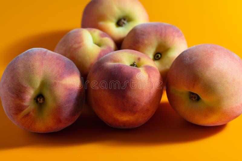 Saftig ny mogen persika på orange matte bakgrund fotografering för bildbyråer