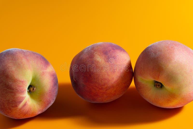 Saftig ny mogen persika på orange matte bakgrund arkivfoton