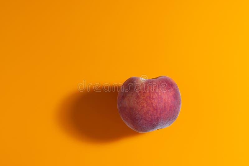 saftig ny mogen persika på orange matte bakgrund arkivbild