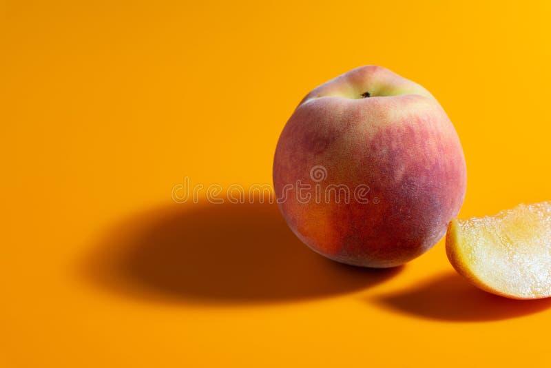 saftig ny mogen persika på orange matte bakgrund royaltyfria bilder