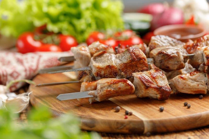 Saftig och aptitretande kebab från griskött som lagas mat på öppen brand och nya grönsaker Stilleben på en träbakgrund arkivfoton