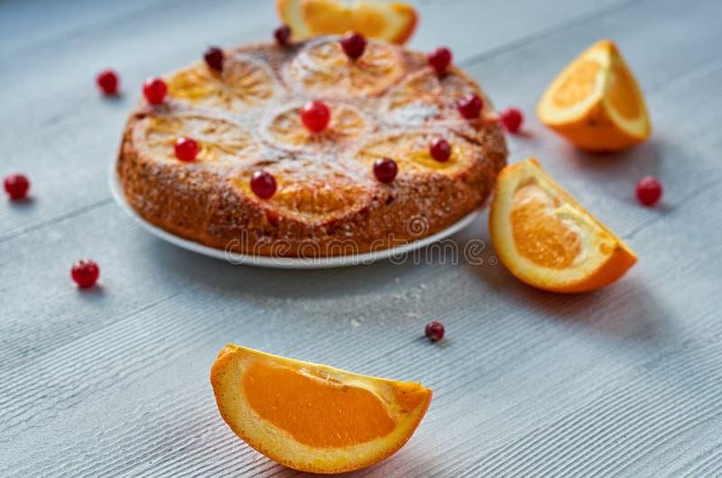 Saftig orange skiva på förgrundsslutet upp Hemlagad orange kaka med nya röda tranbär, apelsiner på den suddiga bakgrunden royaltyfria bilder