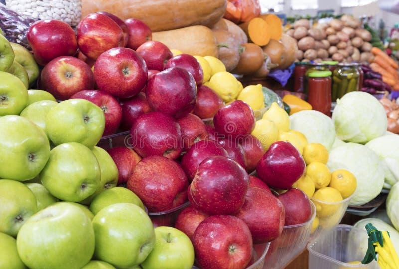Saftig vom grünen, roten Apfelhintergrund, trägt gelbe Zitronen und anderes Gemüse für Verkauf auf dem Markt Früchte stockfoto