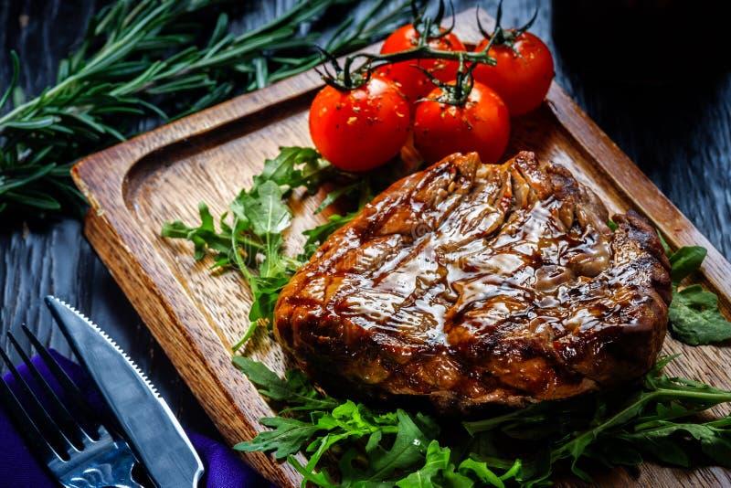 Saftiga delar av grillad filébiff tjänade som med tomater och royaltyfri fotografi