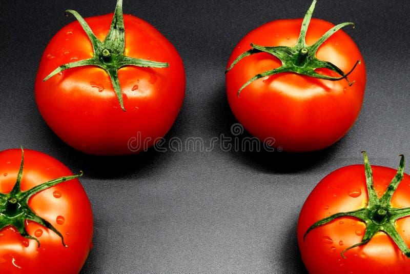Saftiga fyra och mogna tomater ligger på en svart bakgrund arkivfoton