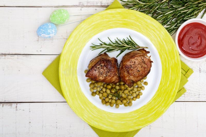 Saftiga grisköttmedaljonger som slås in i bacon, serve med gröna ärtor och en kvist av rosmarin royaltyfri bild