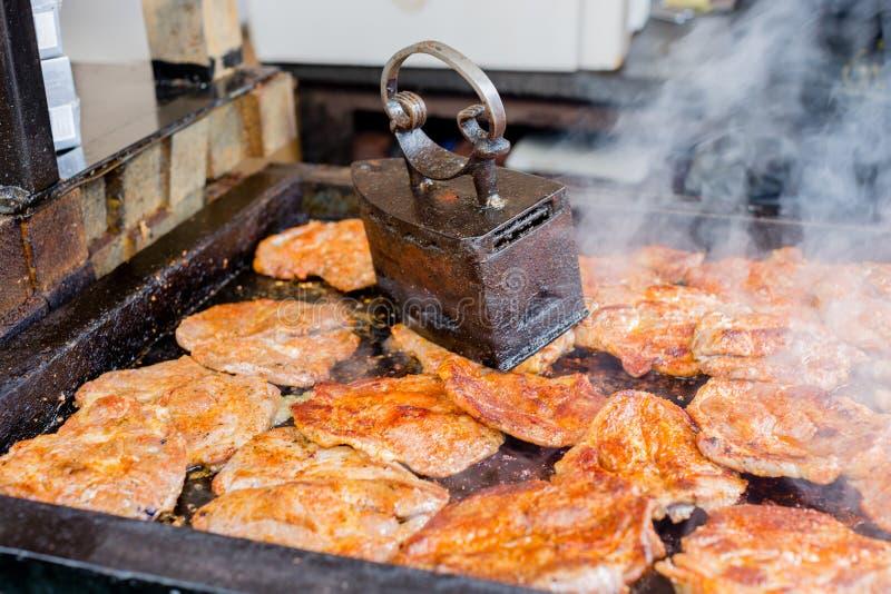 Saftiga köttbiffar som grillar på grillfest under press för tappningjärngaller på gatamatfestivalen arkivbilder