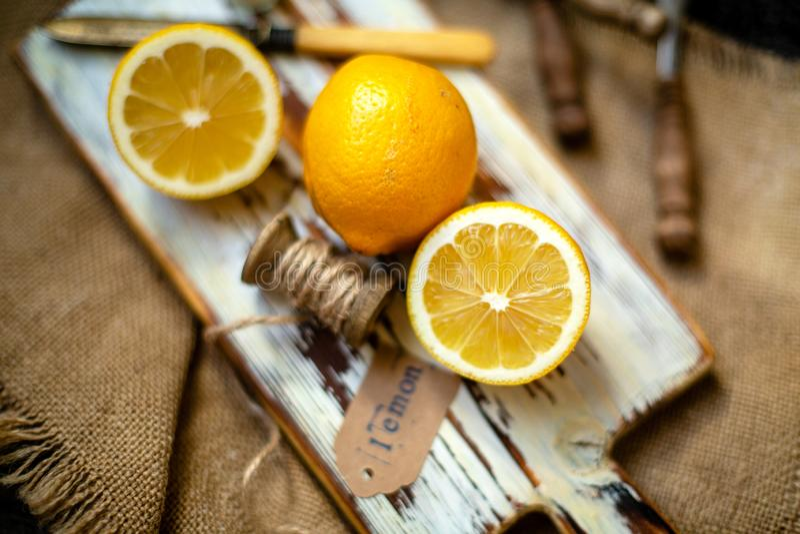 Saftiga mogna citroner på lantligt träbrunt vitt bräde på säckväv med tappningkniven arkivbilder
