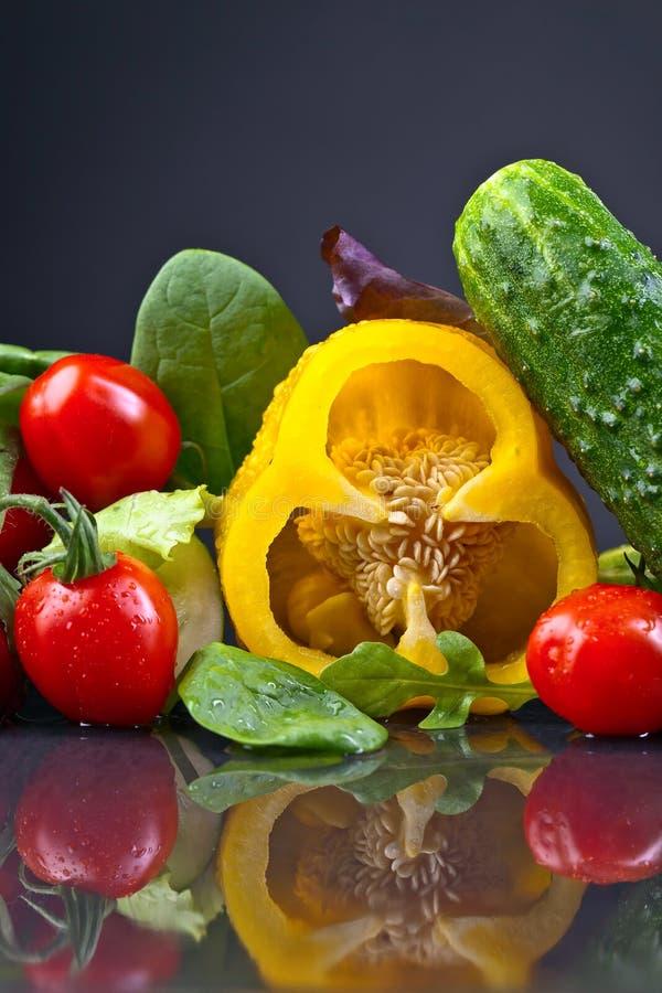 Saftiga mogna grönsaker med arugula och spenat på den svarta tabellen royaltyfria bilder
