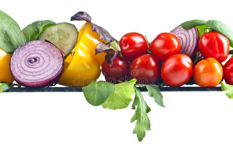 Saftiga mogna grönsaker med arugula och spenat på den vita backgroen royaltyfri foto