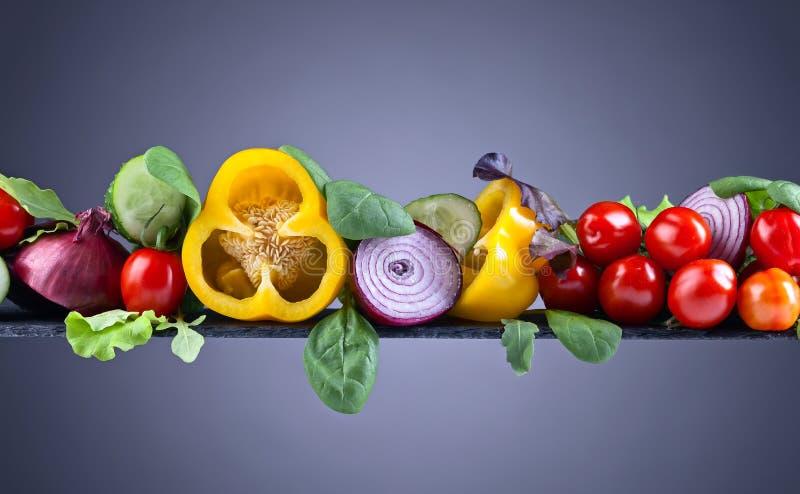 Saftiga mogna grönsaker med arugula och spenat på den vita backgroen royaltyfri fotografi