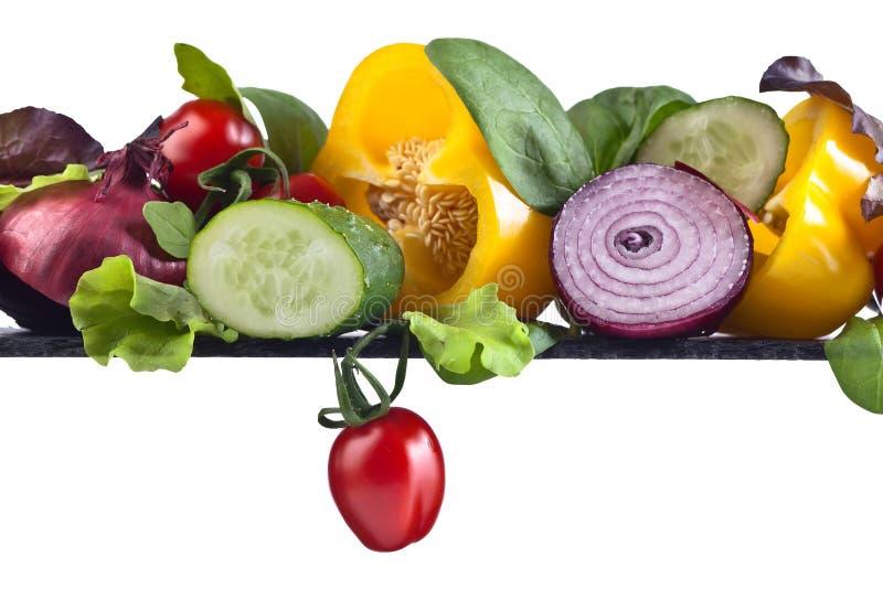 Saftiga mogna grönsaker med arugula och spenat på den vita backgroen fotografering för bildbyråer