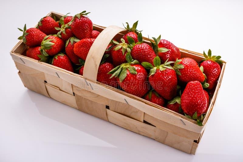 Saftiga nya jordgubbar i en träkorg royaltyfri fotografi
