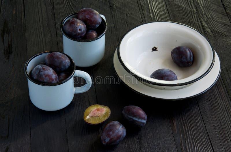 Saftiga plommoner i enamelware fotografering för bildbyråer