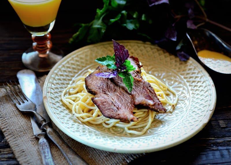 Saftiga stycken av kött på en platta med spagetti, basilikasås, persilja, tappningkniven och gaffeln på en servett på den mörka b arkivbild