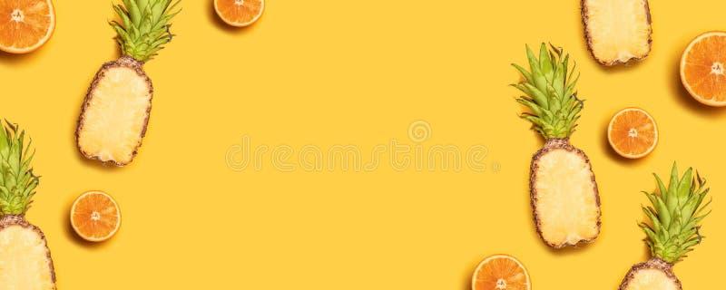 Saftiga tropiska frukter p? en gul bakgrund: apelsiner kokosn?tter, citroner, ananors arkivbilder