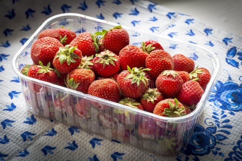 Saftige Erdbeeren in einem Behälter auf einer Tischdecke lizenzfreie stockfotografie