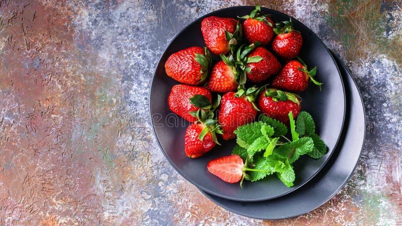 Saftige Erdbeeren und Minze auf einer Schattenplatte auf einem rostigen Hintergrund Beschneidungspfad eingeschlossen lizenzfreies stockbild