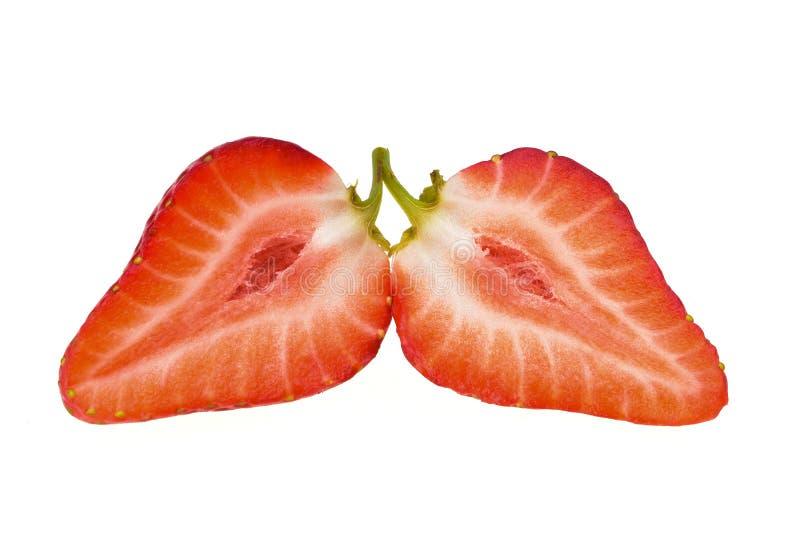 Saftige frische Erdbeeren, spalteten sich in zwei Hälften und durch einen grünen Zweig verbunden auf stockfotografie
