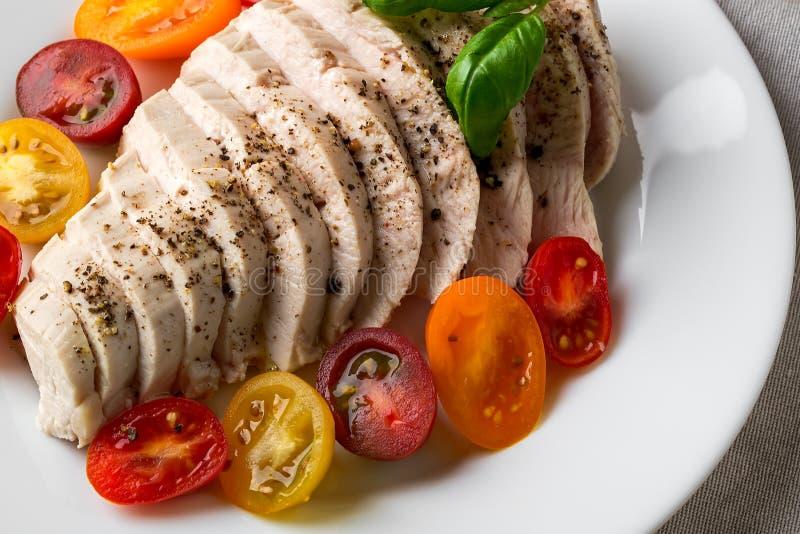 Saftige Hühnerfilet, bei niedriger Temperatur im Vakuum gekocht Geschnittene Hühnerbrust und halbe frische Kirschtomaten auf weiß stockbilder