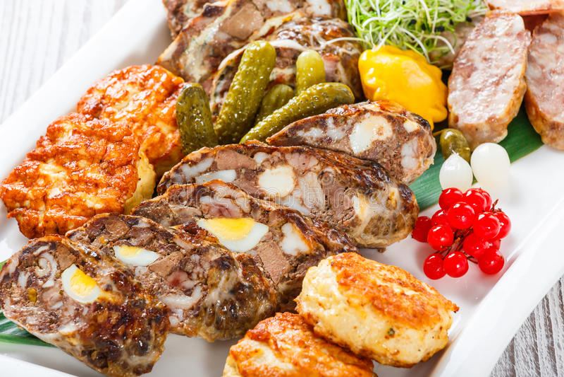 Saftige köstliche Fleischkoteletts und selbst gemachte Wurst mit in Essig eingelegtem Gemüse auf Platte auf hölzernem Hintergrund lizenzfreie stockfotografie