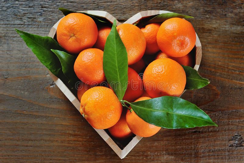 Saftige Klementinen in einem Herzen formten Kasten auf einem hölzernen Hintergrund stockfotografie