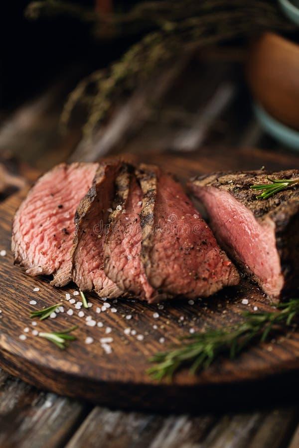 Saftige mittlere Rindfleisch-Rib Eye-Steakscheiben auf hölzernem Brett mit Krautgewürzen und -salz lizenzfreies stockfoto