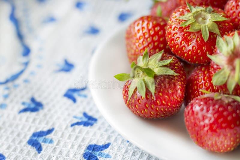 Saftige reife Erdbeere auf einer weißen Platte stockbilder