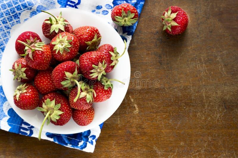 Saftige reife Erdbeere auf einer weißen Platte, die auf einer Weinlesetabelle steht lizenzfreie stockfotografie