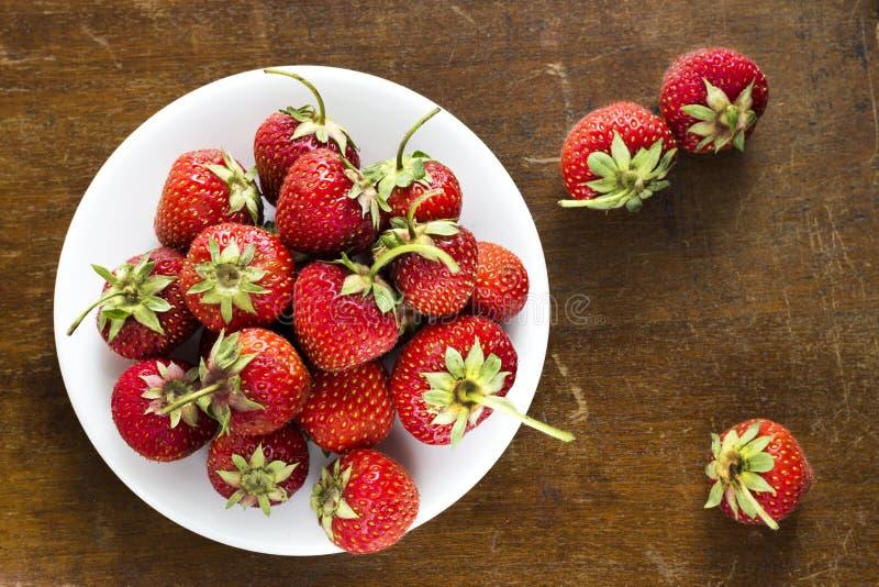 Saftige reife Erdbeere auf einer weißen Platte, die auf einer Weinlesetabelle steht lizenzfreie stockfotos