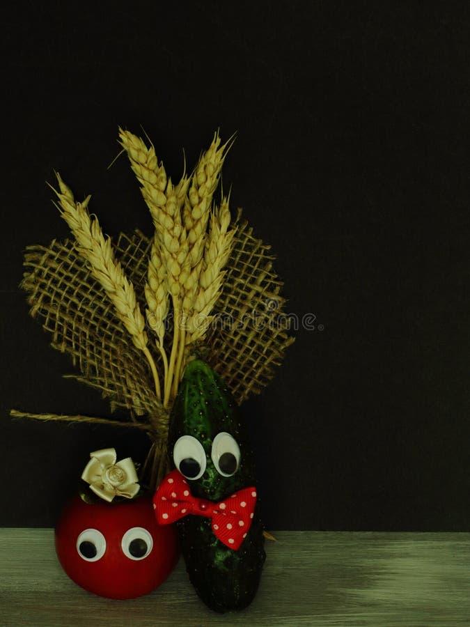 Saftige rote Tomate mit der dekorativen Blume gemacht von der empfindlichen Seide und von der Gurke mit heller Fliege und Blumens lizenzfreie stockbilder