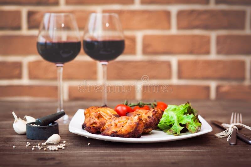 Saftige Stücke der gegrillten Fleischleiste dienten mit Kirschtomaten Niederlassung und Kopfsalat auf einer weißen Platte, Glas R stockbild