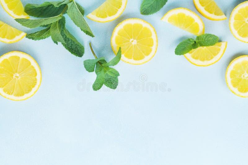 Saftige Zitronenscheiben und tadellose Blätter auf blauer Tischplatteansicht flache Lageart lizenzfreie stockfotografie