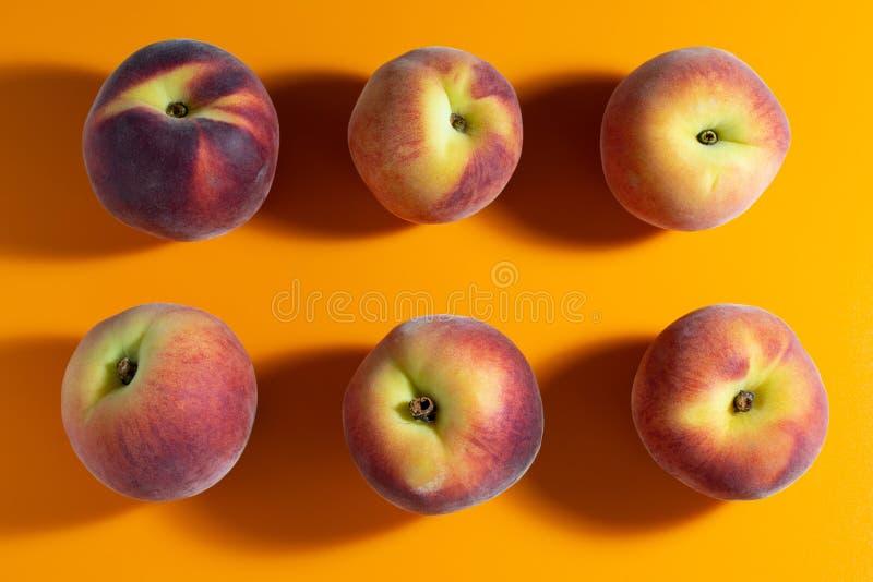 saftiger frischer reifer Pfirsich auf orange Matthintergrund lizenzfreies stockbild