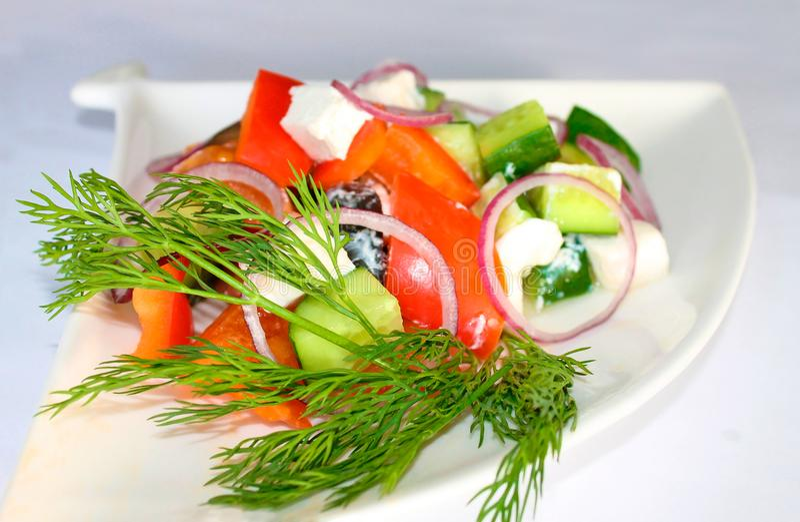 Saftiger griechischer Salat auf einer weißen dreieckigen Platte lizenzfreie stockfotografie