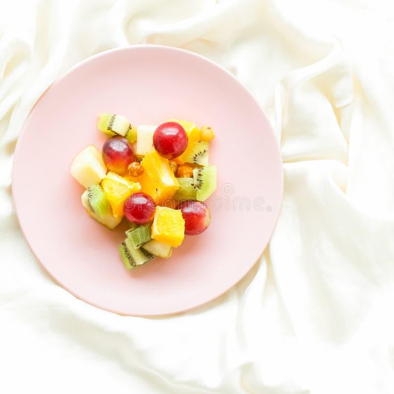 saftiger Obstsalat auf der Seide, flatlay - gesunder Lebensstil und Frühstück im Bettkonzept stockfotos