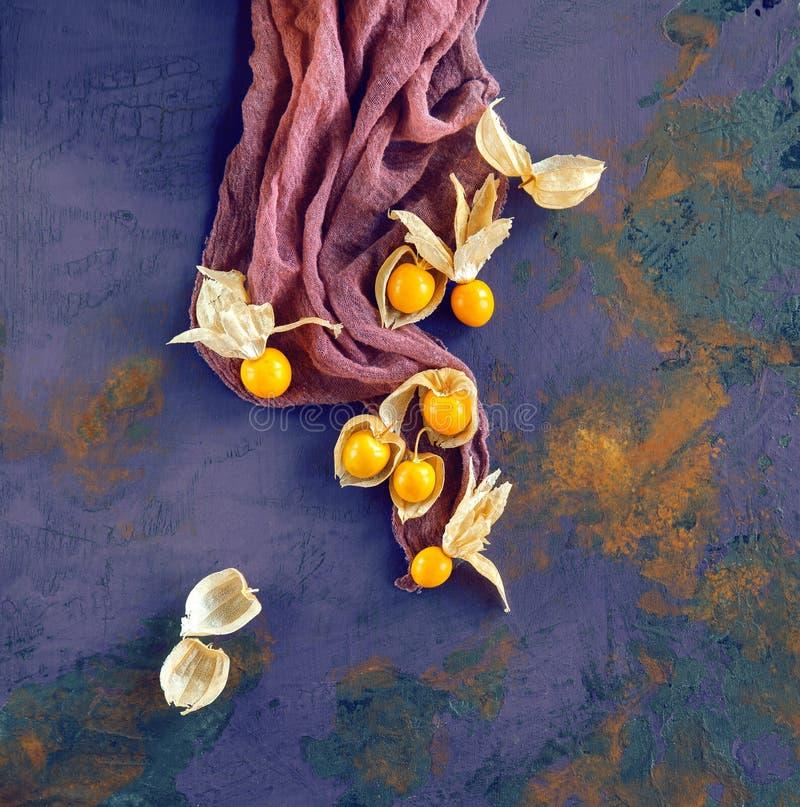 Saftiger reifer, gelber Physalis auf rustikalem hölzernem Brett mit Stoff lizenzfreie stockfotografie