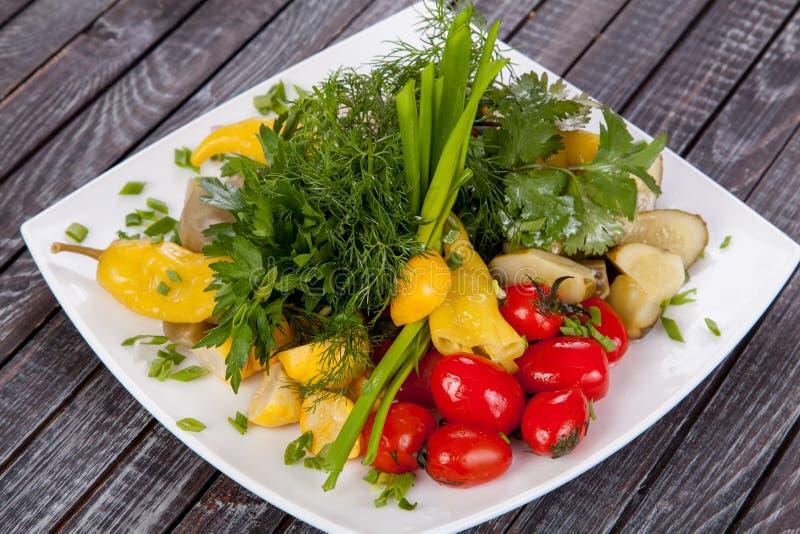 Saftiger, Sommergemüsesalatausschnitt vom Frischgemüse und Grüns in einer schönen Umhüllung auf einem Holztisch stockfoto