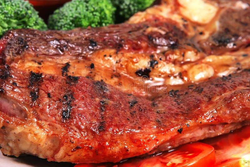 Saftiges fettes Steak des Bratens und heiße Soßen stockfoto