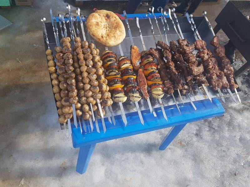 Saftiges mariniert im Gewürzfleischkebab auf Aufsteckspindeln, gekocht und auf einem Feuer- und Holzkohlengrillgrill, in Form sch lizenzfreies stockfoto