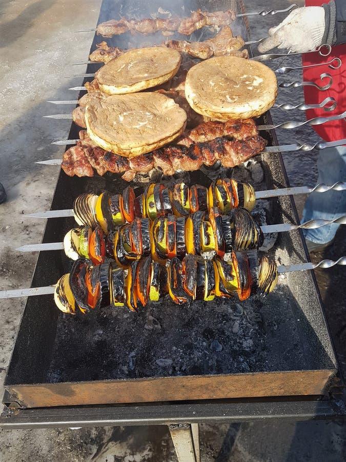 Saftiges mariniert im Gewürzfleischkebab auf Aufsteckspindeln, gekocht und auf einem Feuer- und Holzkohlengrillgrill, in Form sch lizenzfreie stockfotografie
