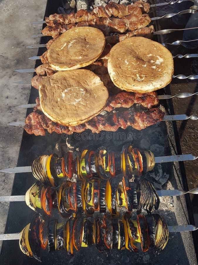 Saftiges mariniert im Gewürzfleischkebab auf Aufsteckspindeln, gekocht und auf einem Feuer- und Holzkohlengrillgrill, in Form sch lizenzfreie stockbilder